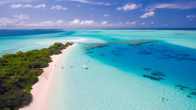 Nádherné tropické, nebesky modré moře s pobřežím, písečnou pláží, stromy a kotvící menší lodí
